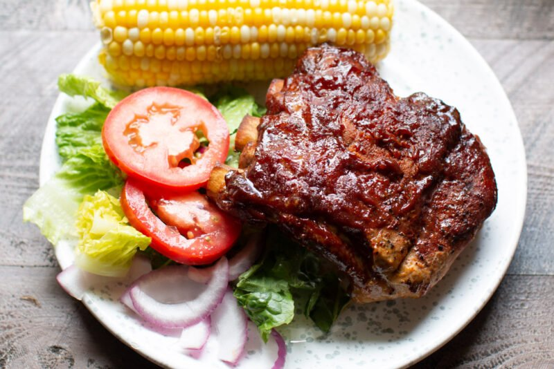 Ribs on a plate with salad and corn
