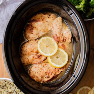 5 chicken breasts in a slow cooker with lemons on top.