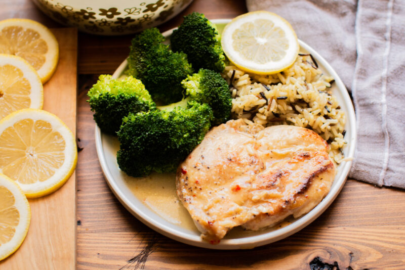 Gray plate with lemon chicken breast, broccoli and rice pilaf.