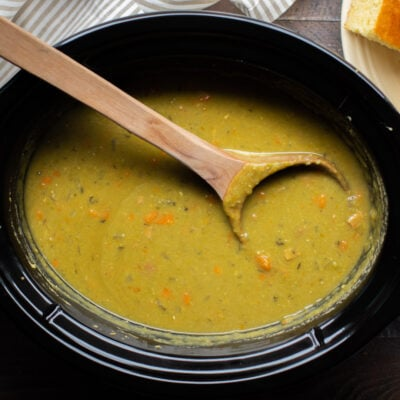 bright green split pea soup in a slow cooker with a wooden spoon in it.
