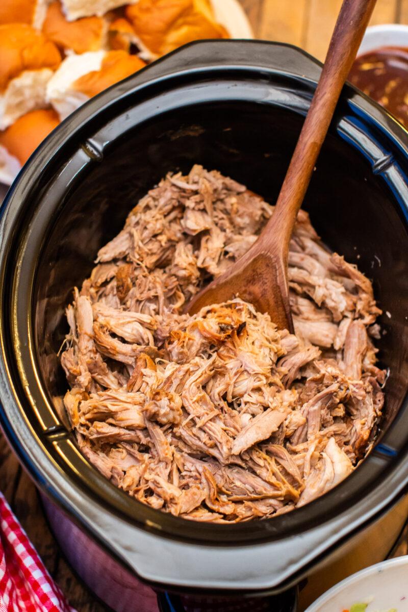 full slow cooker of shredded pulled pork