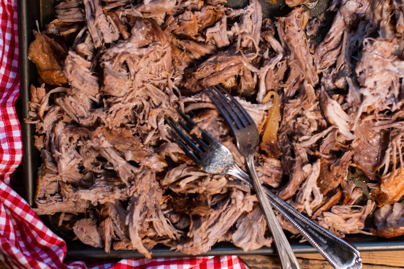 shredded pulled pork on sheet pan with 2 forks on top