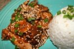 sesame chicken with sesame seeds and green onion on top.