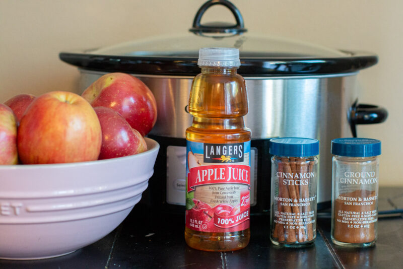 Apples, apple juice, cinnamon and cinnamon sticks in front of a slow cooker.