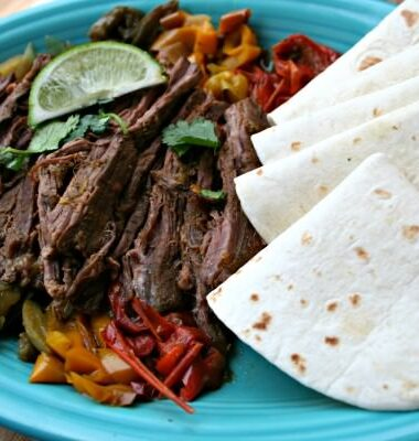 Steak Fajitas with tortillas on plate