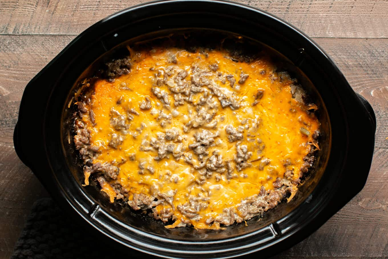 Cooked tater tot casserole in slow cooker with cheese on top.