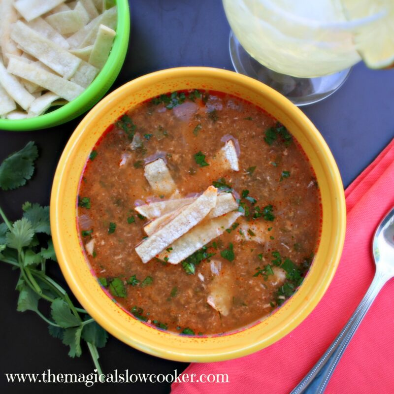 Chicken tortilla soup in yellow bowl with tortilla strips on top