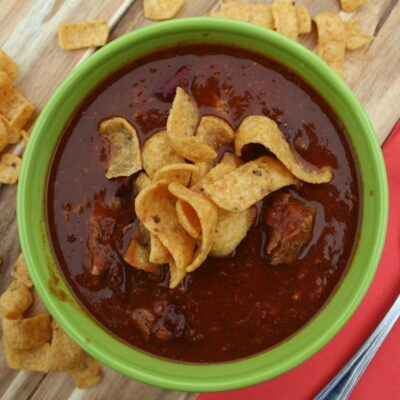 Chili in green bowl with fritos on top.