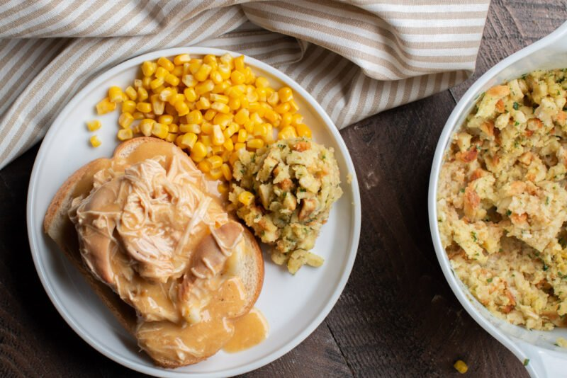 Plate of bread, mashed potatoes and chicken and gravy on top. Corn and stuffing on the side.