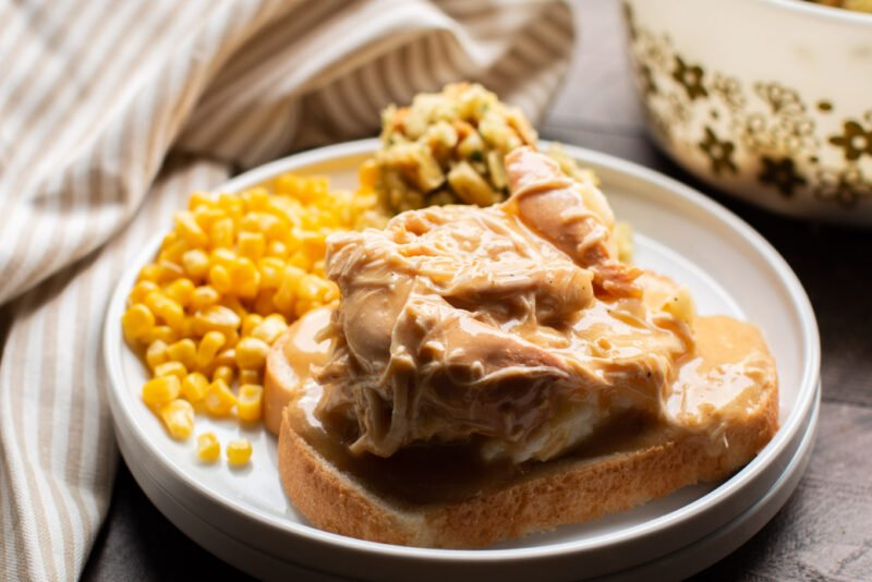 Close up of bread, mashed potatoes, chicken and gravy.