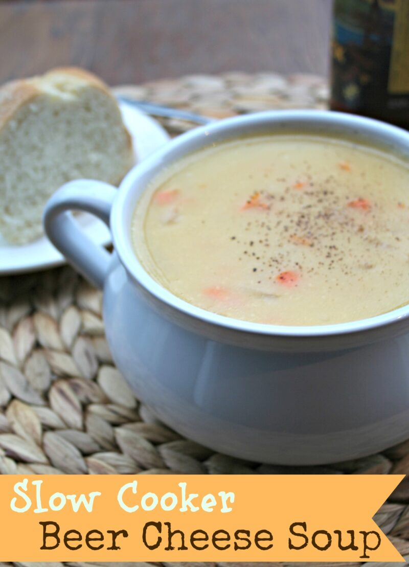 Beer Cheese Soup in white bowl with bread on side