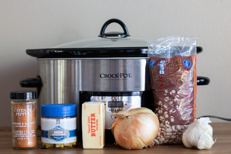 slow cooker with pinto beans, chicken bouillon, yellow onion, garlic and cayenne pepper in front of it.