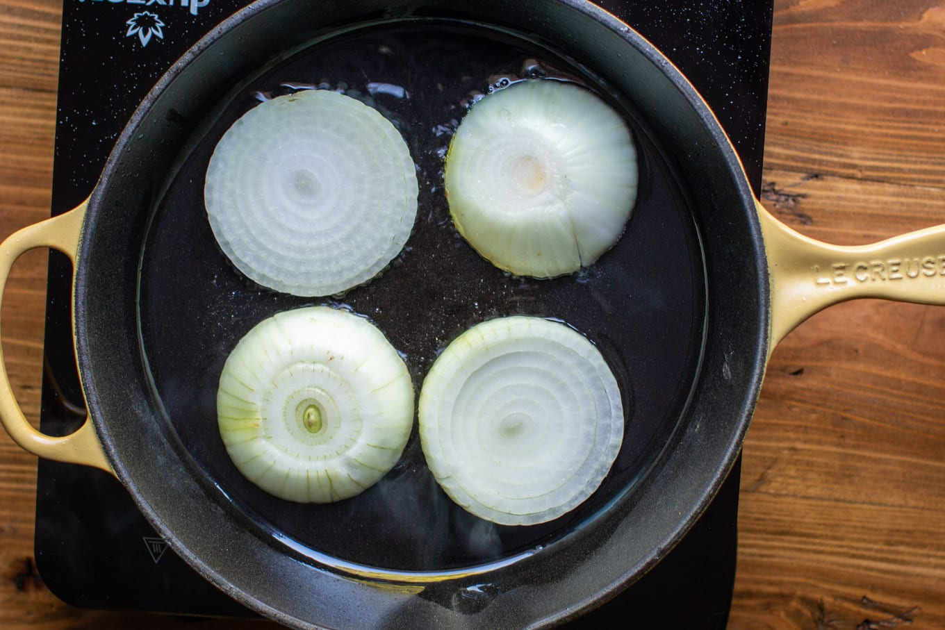4 slices of yellow onion frying in a cast iron pan.