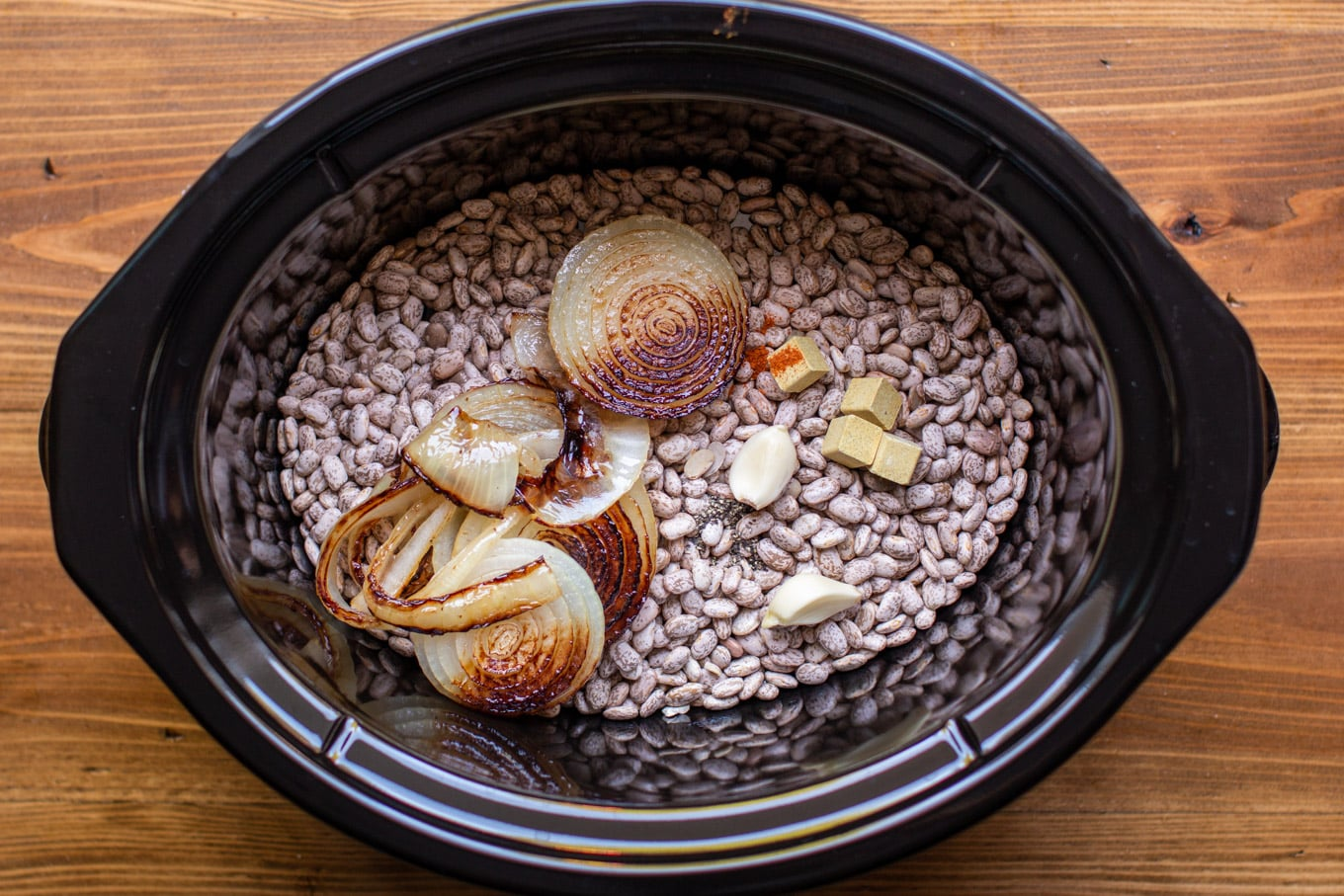 pinto beans in a slow cooker with fried onions, garlic, cayenne pepper and chicken bouillon cubes.
