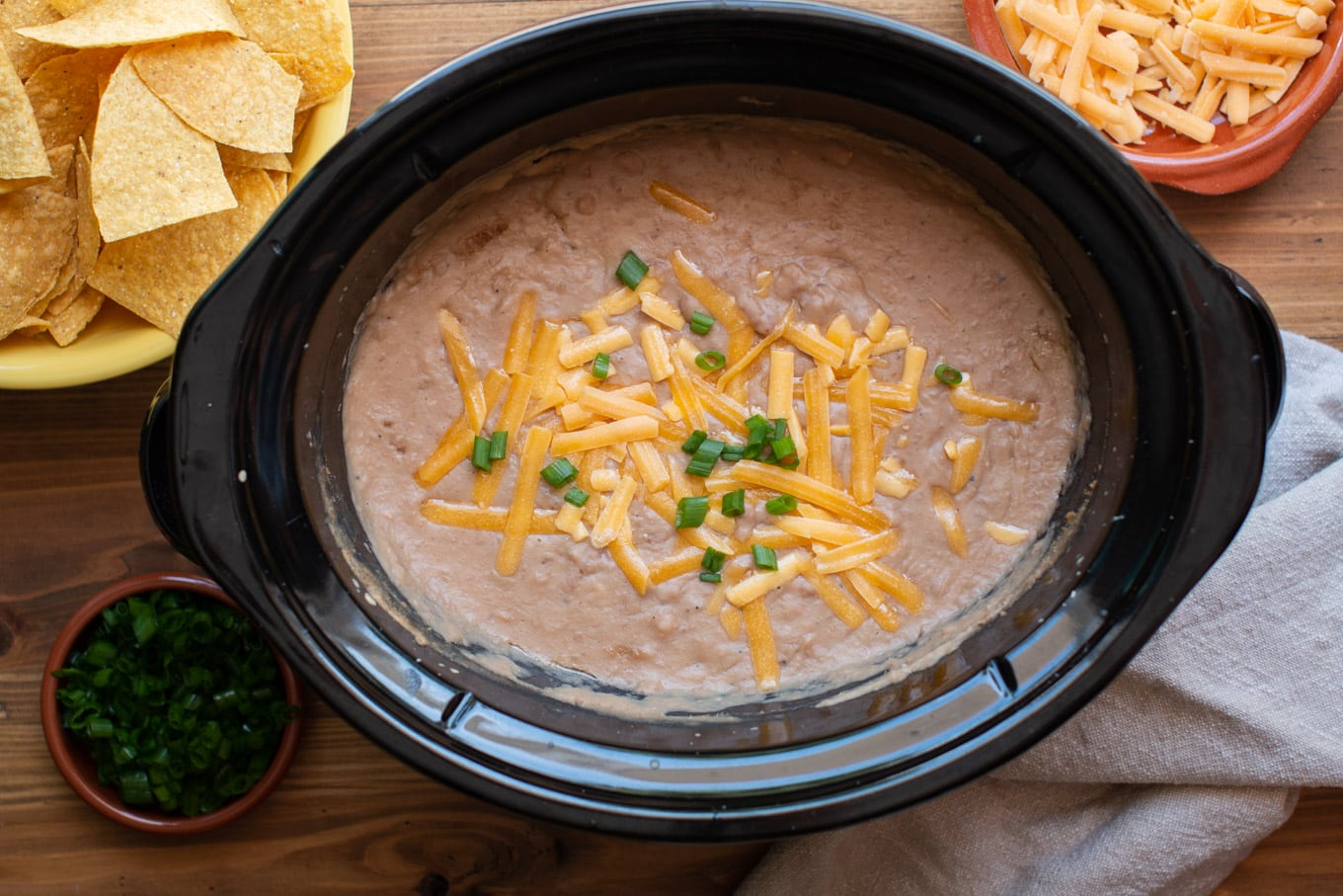 pureed pinto beans in a slow cooker with chips and cheese on the side.