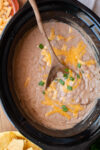 refried beans in a slow cooker with a wooden spoon in it.