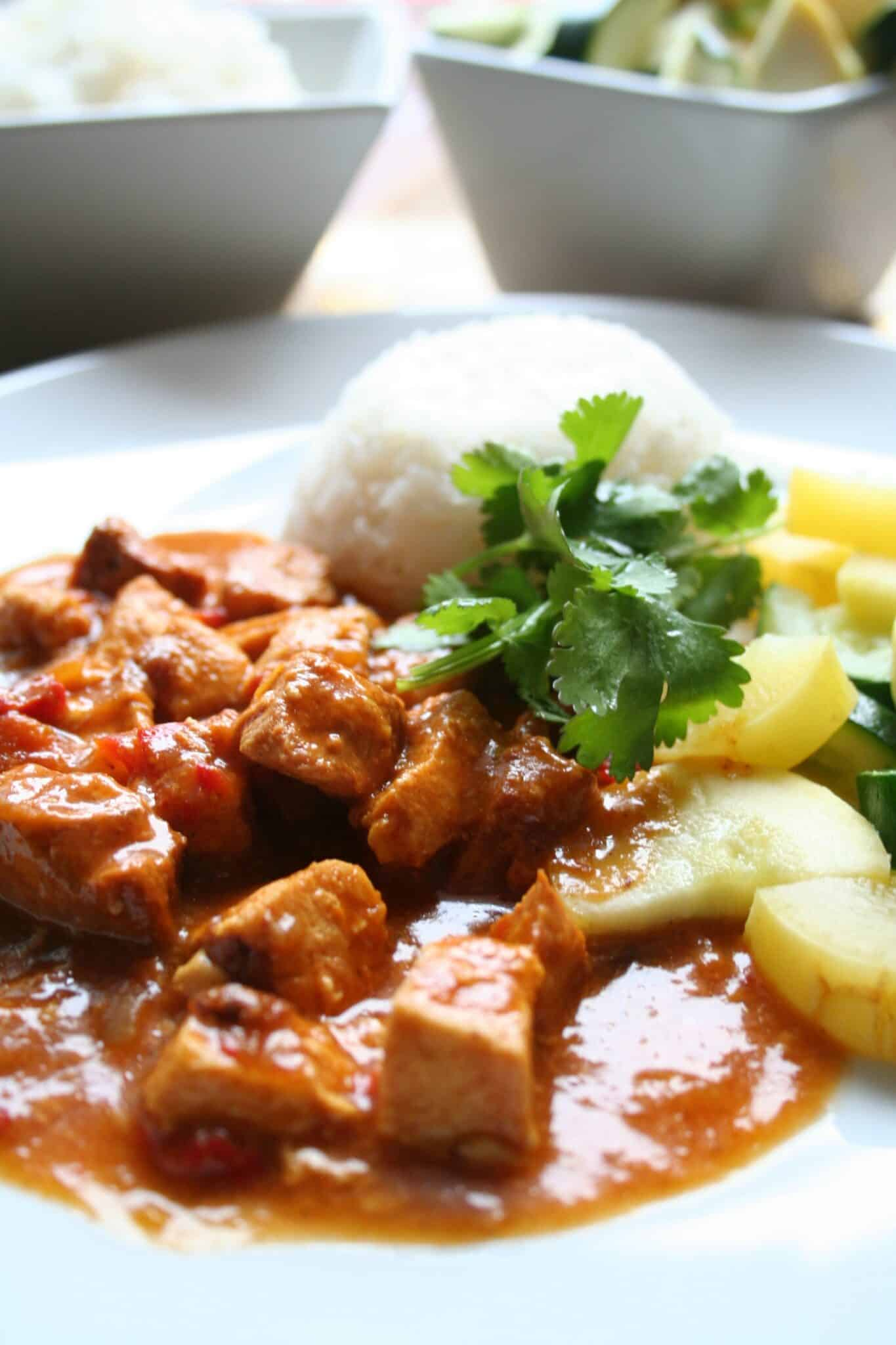 Chicken curry on plate with rice and zucchini