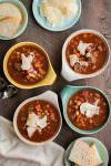 4 bowls of hearty Italian beef soup with parmesan on top