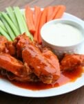 buffalo wings on plate with vegetables and blue cheese dressing