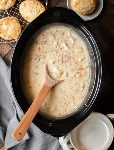 Chicken pot pie filling in slow cooker with spoon in it and biscuits on side