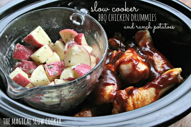 chicken drumsticks in slow cooker with potatoes in glass container on the side of them.