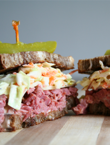 Reuben Sandwich cut in half on cutting board