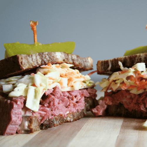 Reuben Sandwich cut in half on cutting board