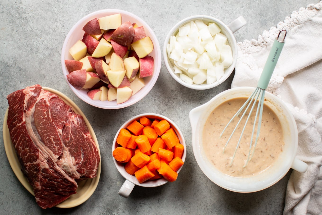 chuck roast, red potatoes, carrots, onion and gravy mixture in dishes on a table.