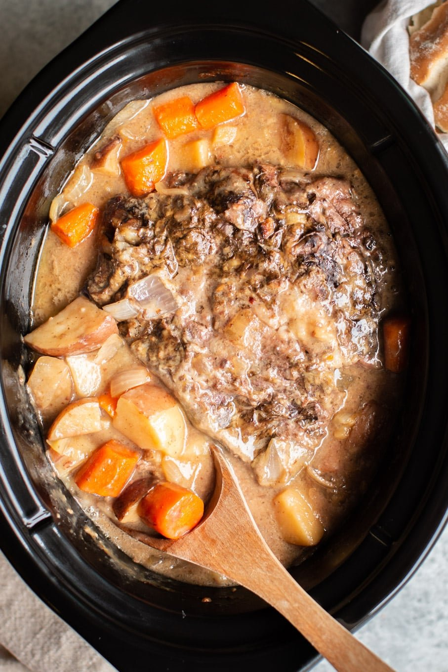 close up of pot roast in gravy in a slow cooker.