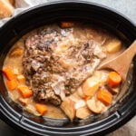 pot roast with gravy, potatoes and onions in a slow cooker with wooden spoon in it.