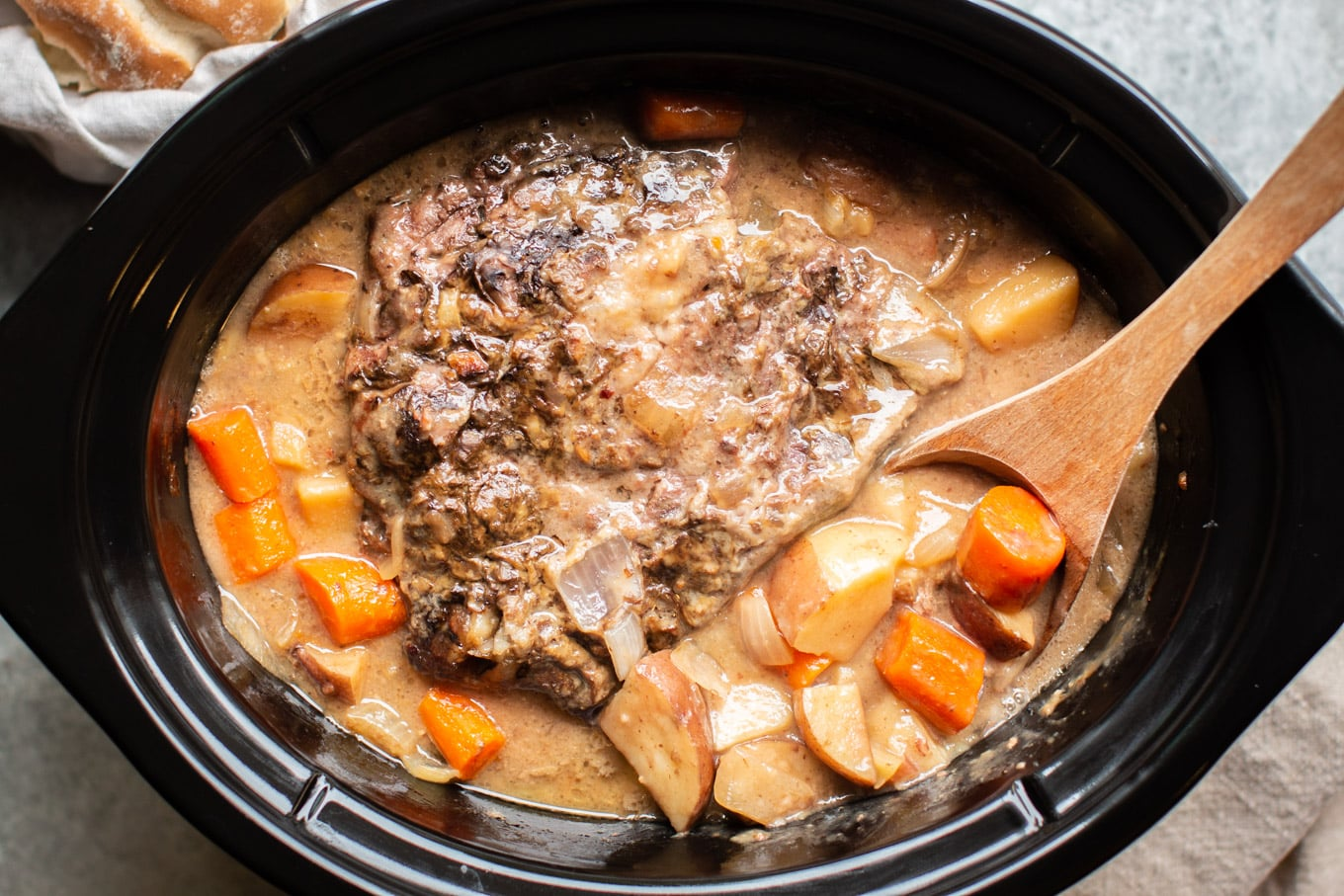 cooked pot roast in gravy with vegetables in a slow cooker.