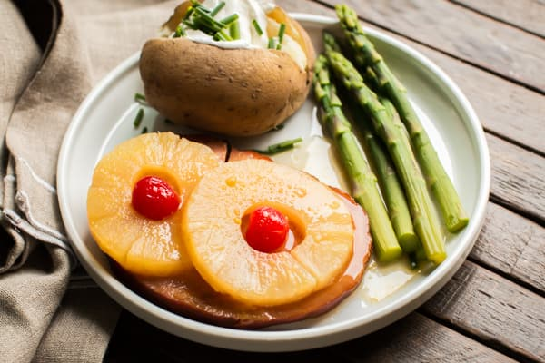 ham with pineapple, baked potato and asparagus on white plate
