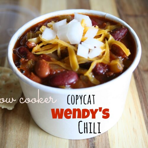 homemade wendy's chili in paper bowl with cheese and onions on top.