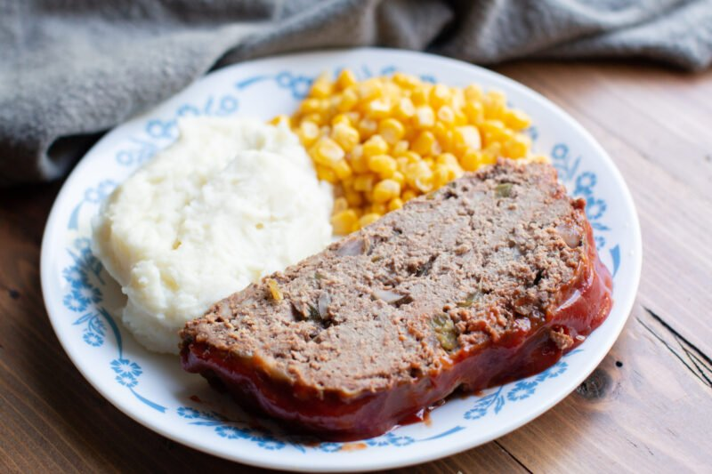 sliced cooked meatloaf on a white plate with mashed potatoes and corn.