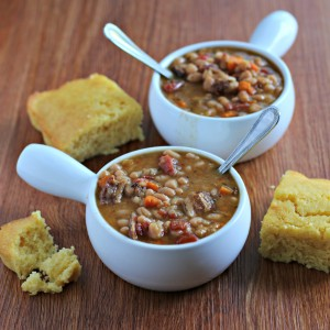 bean and bacon soup in bowls with cornbread on side