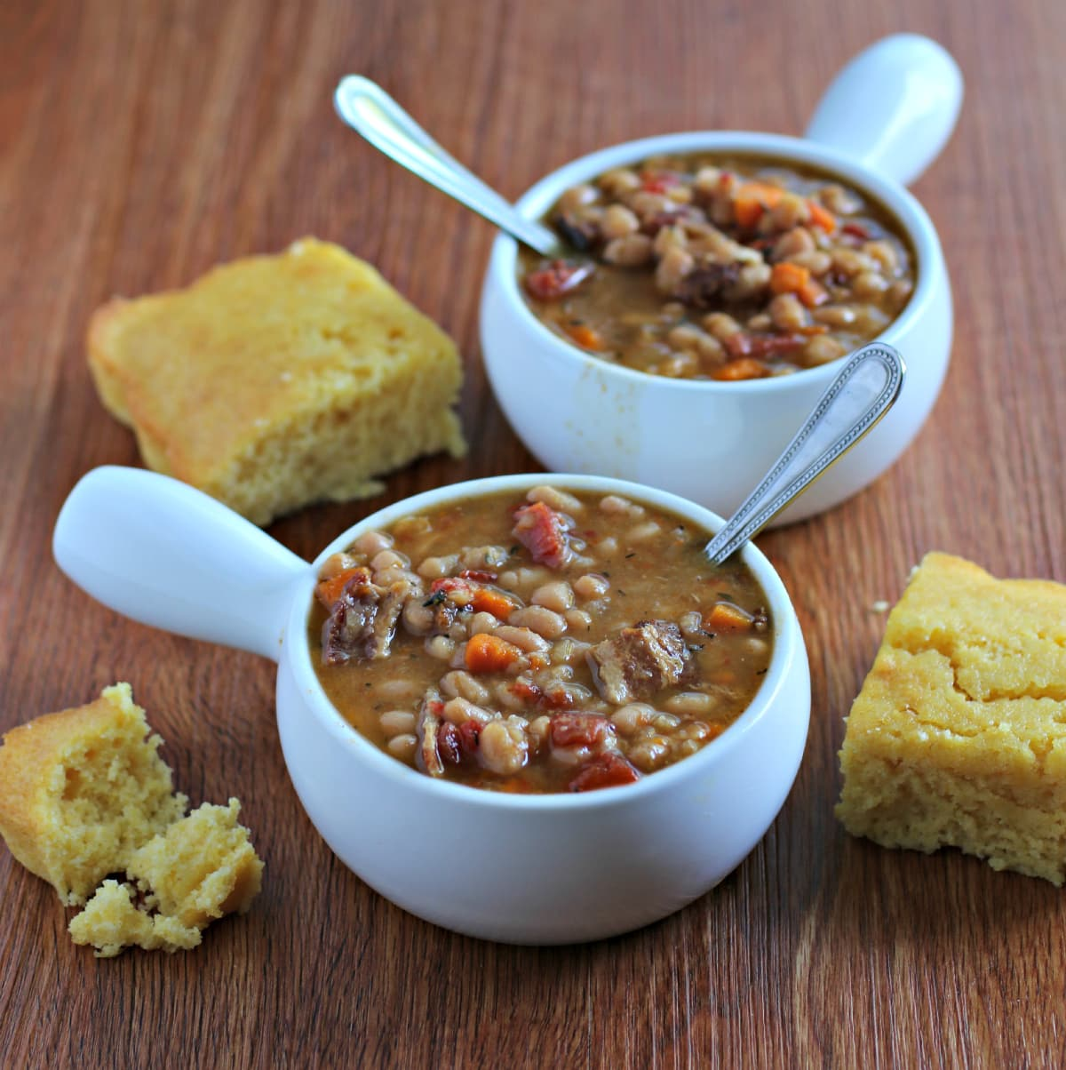 2 bowls of homemade bean and bacon soup with cornbread on side