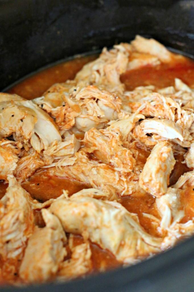 close up of shredded buffalo chicken in crockpot