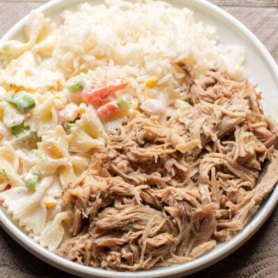shredded pork, pasta salad and white rice on white plate.