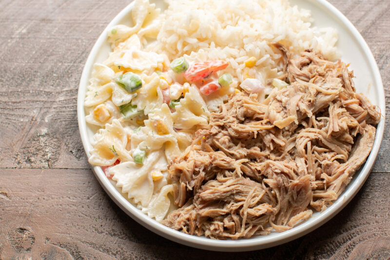 white plate with pasta salad, shredded pork and white rice.