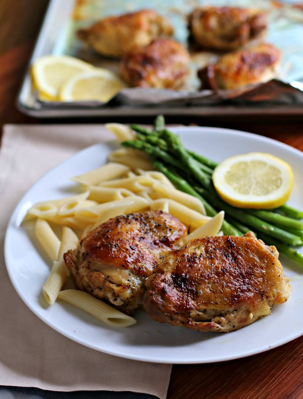 Lemon pepper chicken thighs on a plate with pasta, asparagus and a slice of lemon