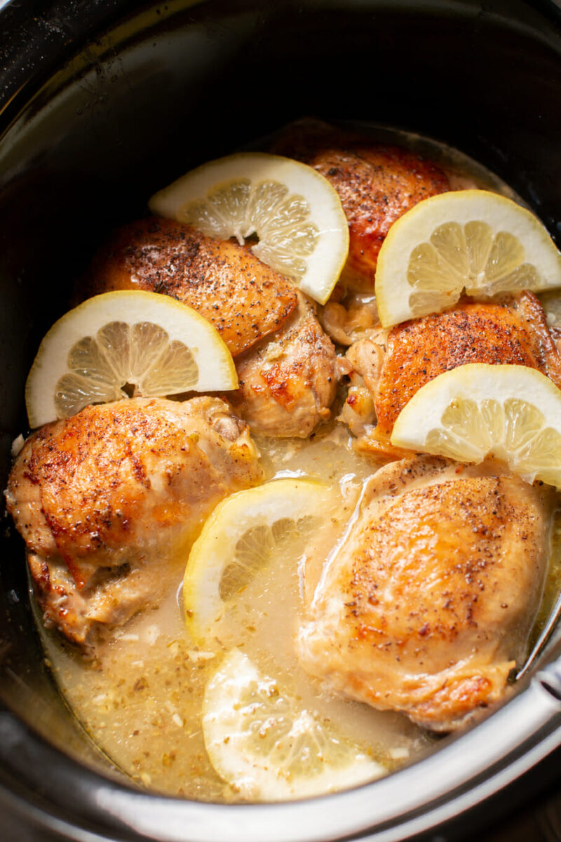 close up lemon pepper chicken thighs in crockpot