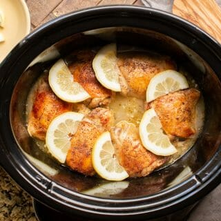 cooked lemon pepper chicken thighs in slow cooker with lemon slices on top.