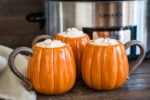 3 pumpkin shaped mugs with whipped cream on top.