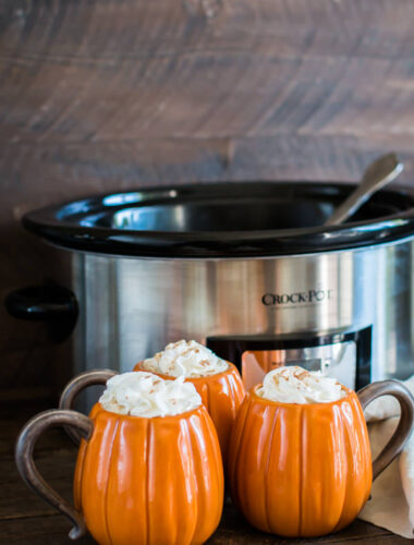 3 pumpkin shaped mugs in front of a slow cooker