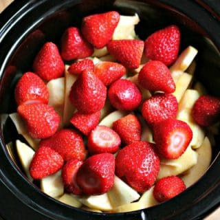 close up of strawberries and sliced apples in slow cooker