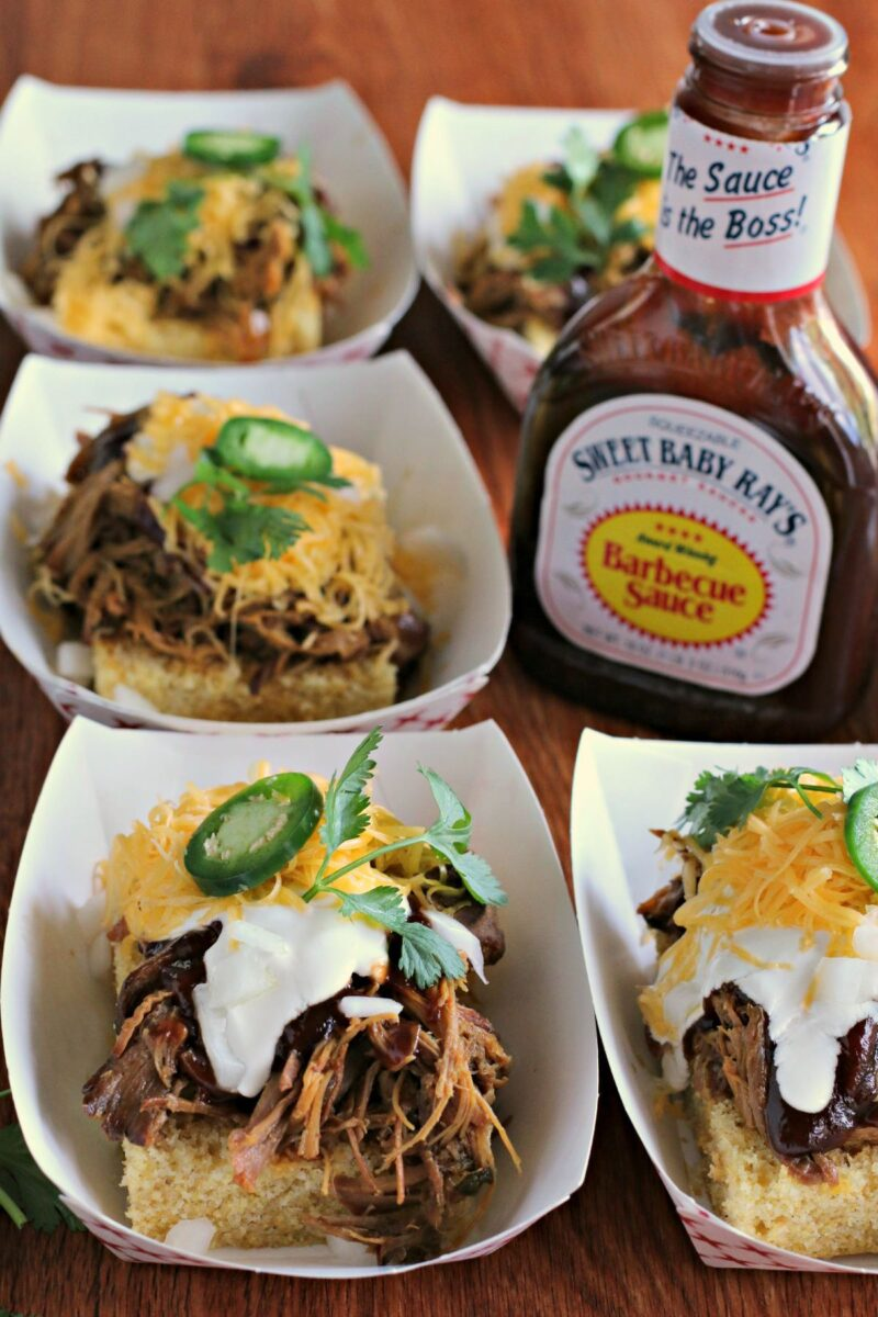 trays of cornbread with pulled pork on top. Bottle of sweet baby ray's barbecue sauce on side.