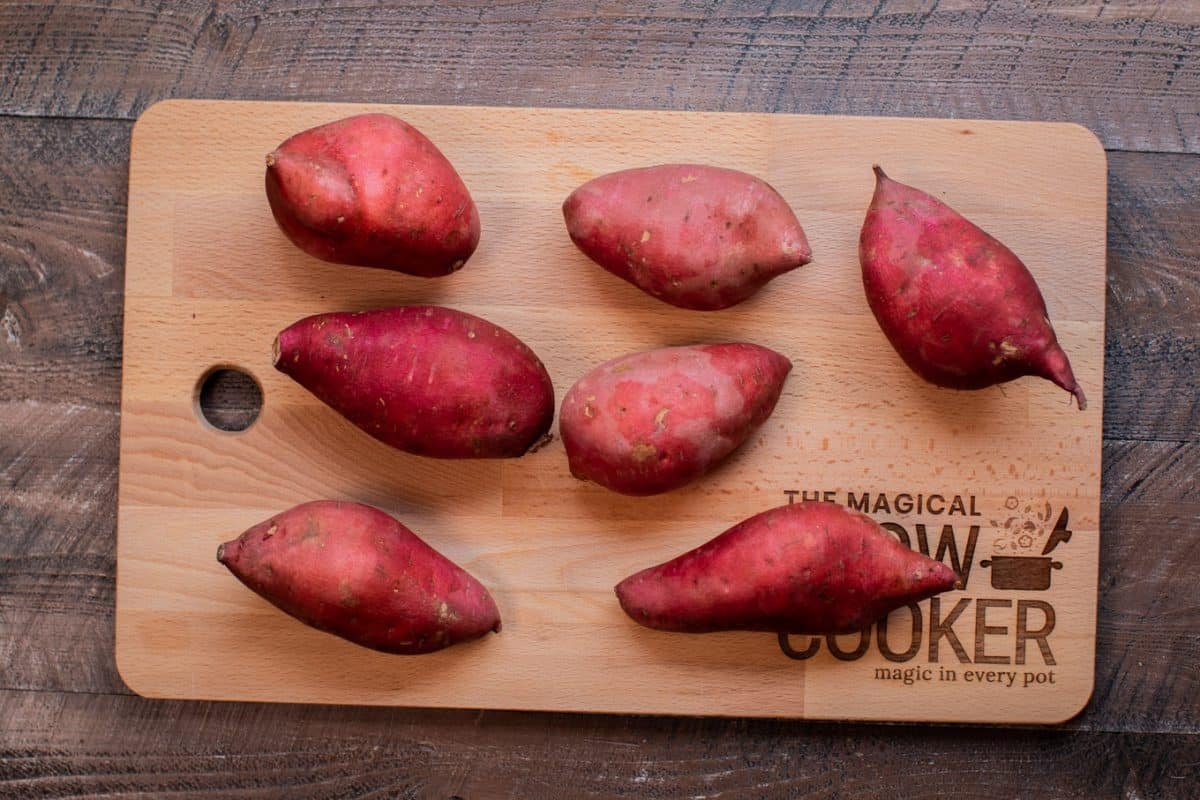 8 uncooked sweet potatoes on a cutting board