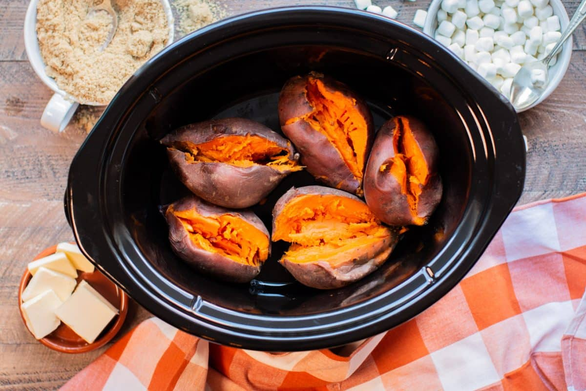 5 sweet potatoes in slow cooker, cooked and slit open