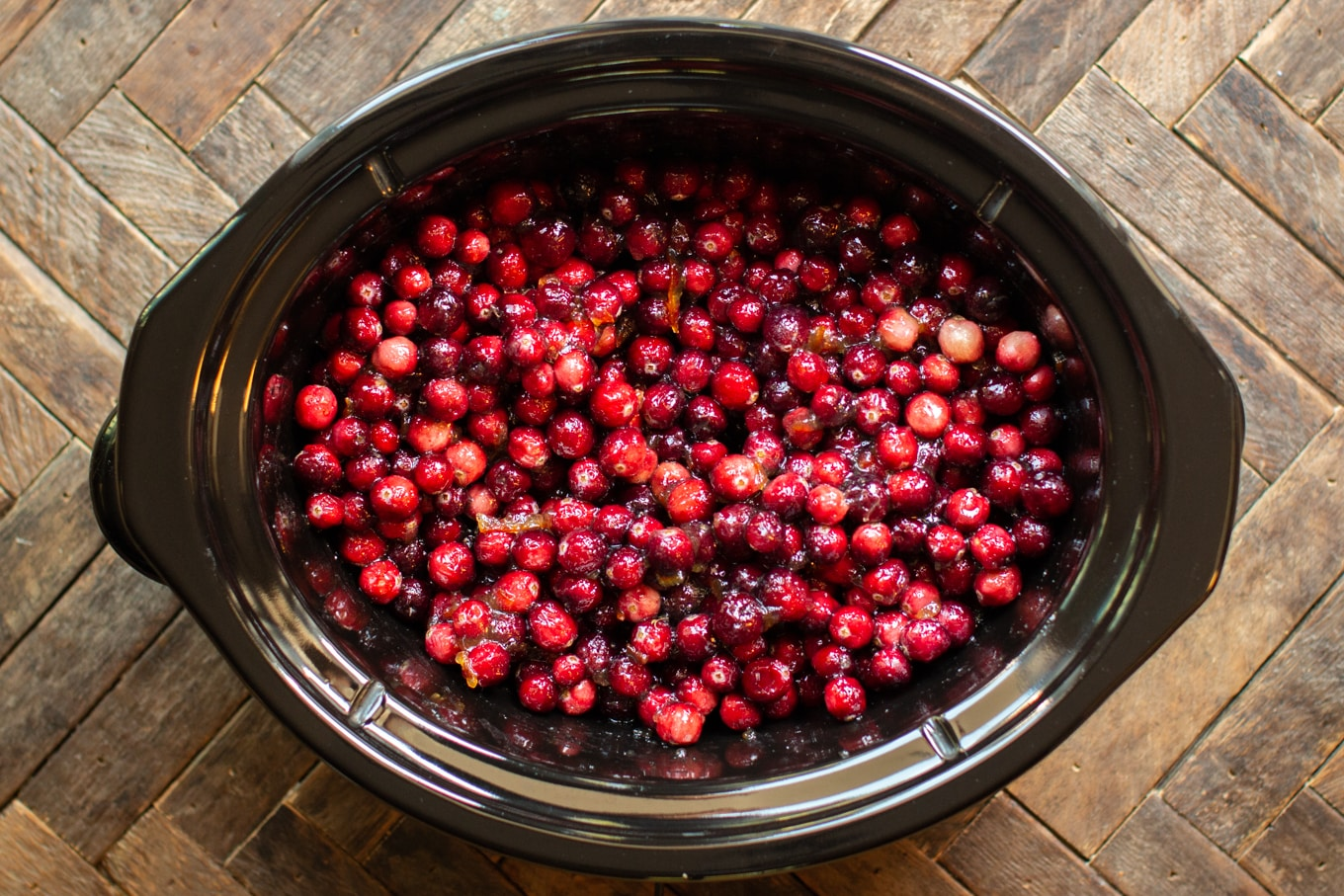 raw cranberries and orange marmalade in a slow cooker.