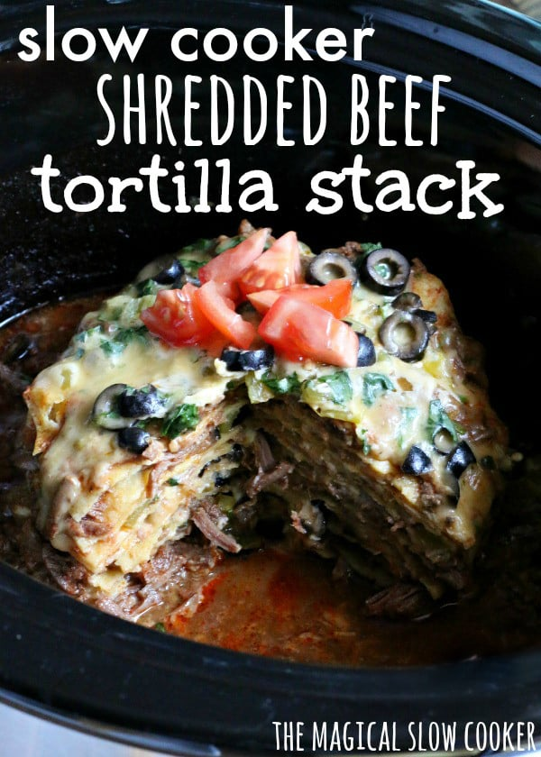 beef and corn tortillas stacked together in slow cooker with cheese, tomato and olives on top.